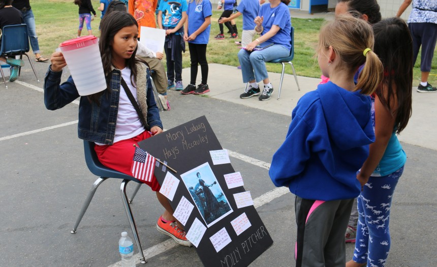 """""""I got my nickname because of how I carried the pitchers of water to the men,"""" Molly PItcher (played by Pamela Herrera) said. She shared her life with First Graders Summer Rainey, Liyah Reguerra and Samantha Enriquez (left to right)."""