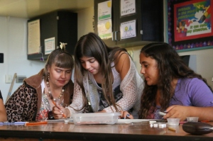 Jeanette Daghestanian (left), is helped with a drawing technique by daughter Olivia Daghestanian as friend Maggie Sidway looks on.